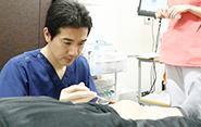 培養幹細胞の注入処置。その後、経過チェックで来院された患者さまの診察を行う。